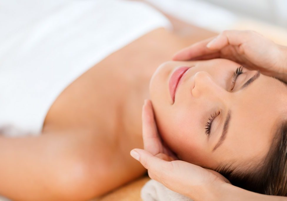 health, beauty, people and relaxation concept - beautiful woman in spa salon getting face treatment