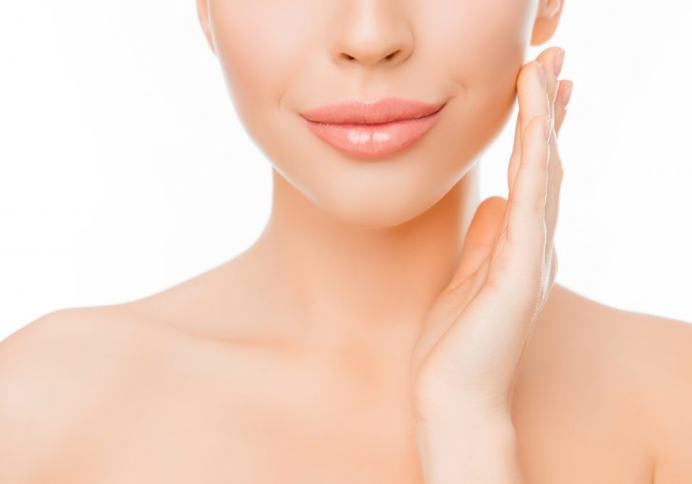 Close up of woman with perfect skin applying cream on face
